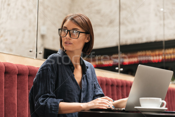 Side view of female manager in eyeglasses sitting by table Stock photo © deandrobot