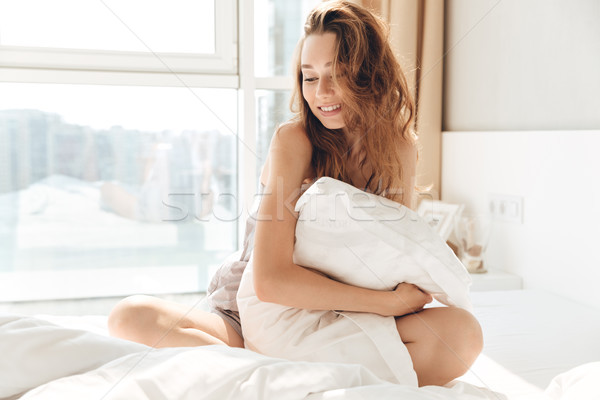 Carefree pretty woman hugging pillow in the morning Stock photo © deandrobot