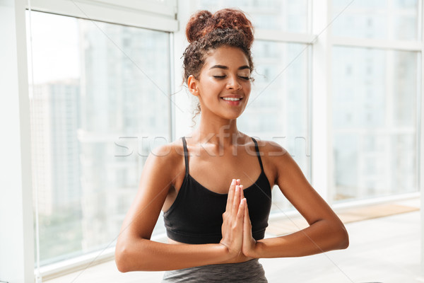 Young lady sitting in lotus pose and meditating Stock photo © deandrobot