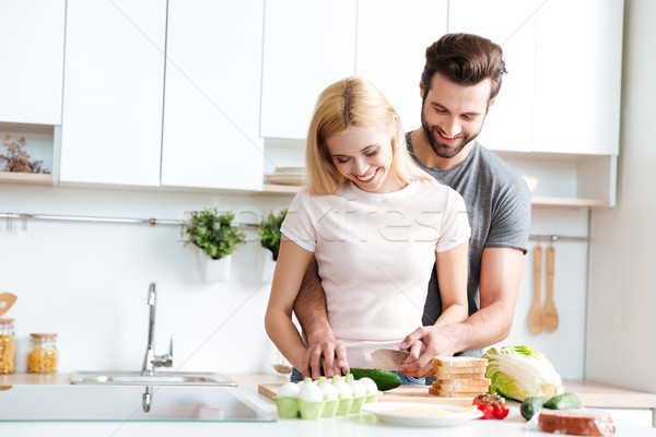 Stock photo: Beautiful smiling couple cooking together in a modern kitchen