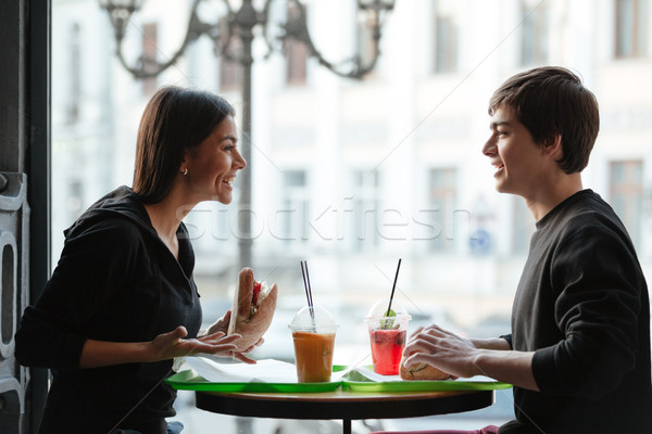 Smiling young man sitting in cafe with sister drinking juice Stock photo © deandrobot