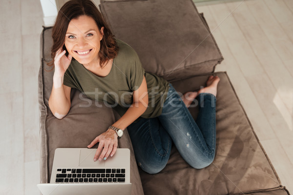 Top view of smiling casual sitting on sofa with computer Stock photo © deandrobot