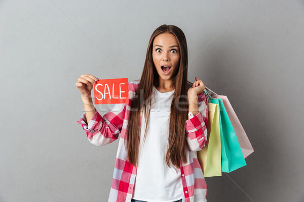 Amazed pretty caucasian woman holding sale sign and shopping bag Stock photo © deandrobot