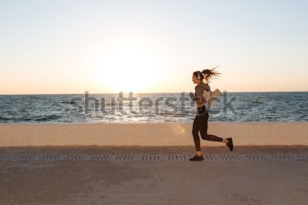 Fit young woman doing stretching workout at the seaside Stock photo © deandrobot