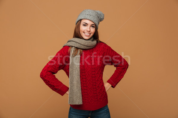 Charming girl in red knitted sweater and woolen hat looking at c Stock photo © deandrobot