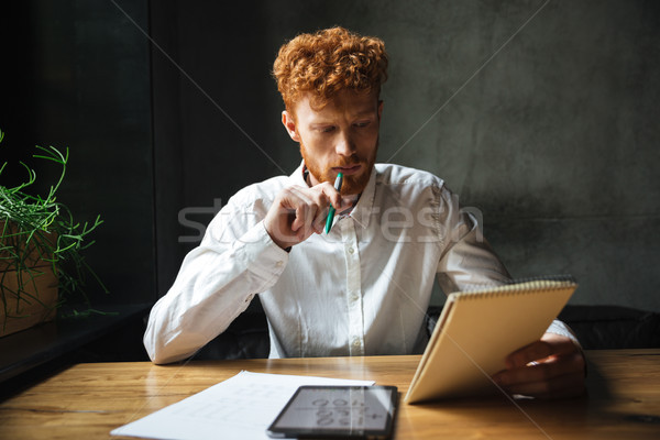 Photo of young thinking readhead bearded man, holding notebook a Stock photo © deandrobot