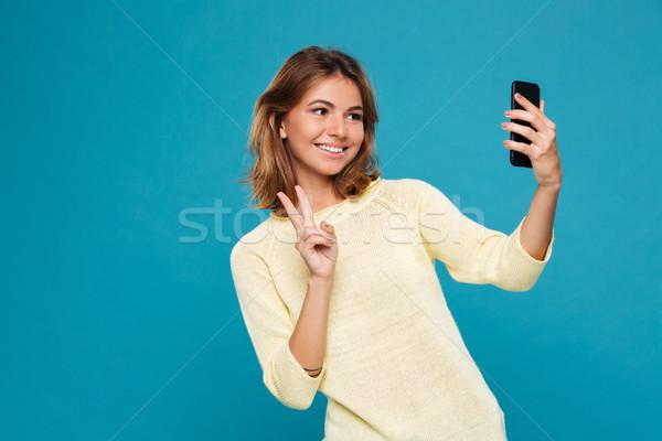 微笑的女人 毛線衣 智能手機 顯示 和平 商業照片 © deandrobot