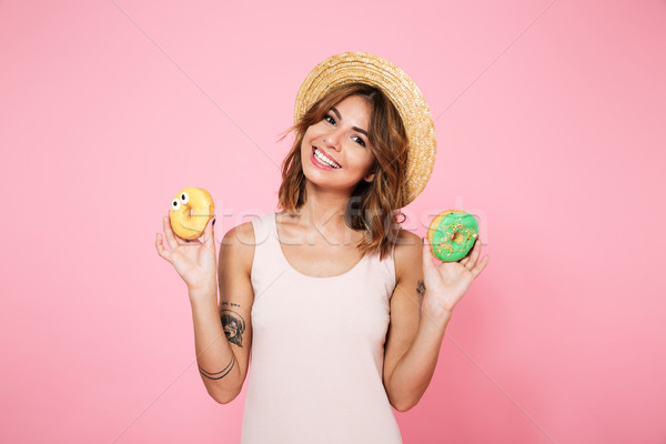 Portrait of a happy smiling woman in hat holding donuts Stock photo © deandrobot