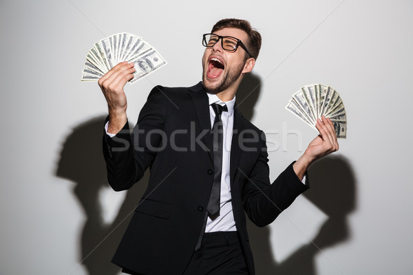 Overjoyed bearded man in black suit holding two bunches of dolla Stock photo © deandrobot