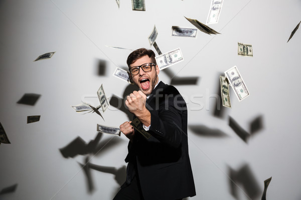 Excited emotional businessman over money. Looking camera. Stock photo © deandrobot