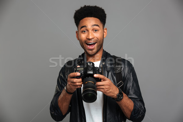 9a867c0b71c Close-up portrait of happy exited afro american man holding phot ...