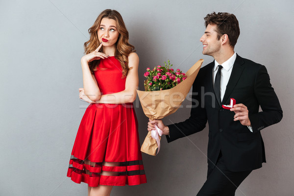 Portrait of a joyful man proposing to a unsatisfied girl Stock photo © deandrobot