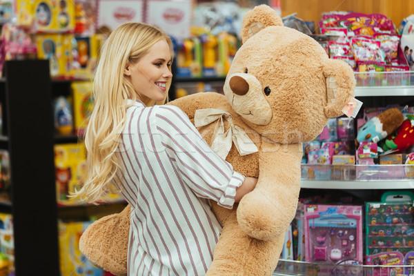 Smiling woman holding big teddy bear Stock photo © deandrobot