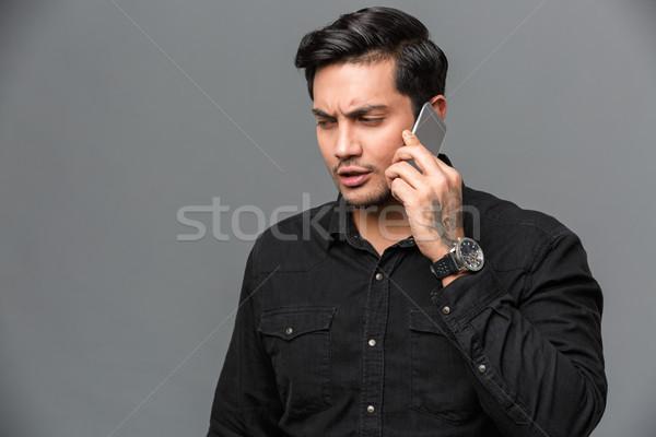 концентрированный молодые красивый мужчина говорить мобильного телефона фото Сток-фото © deandrobot