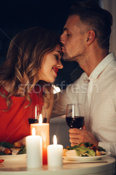 Beautiful man kissing his smiling happy lady while have romantic dinner Stock photo © deandrobot