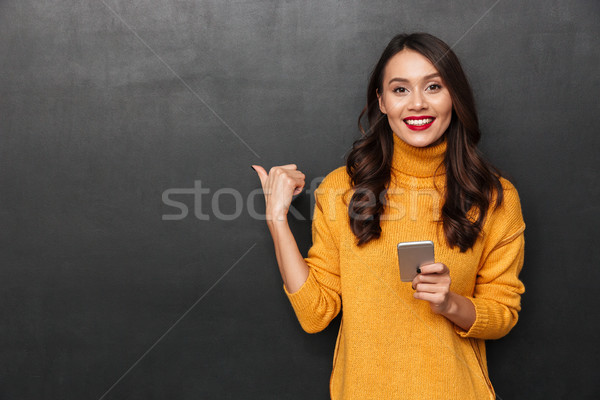 Sorridere bruna donna maglione smartphone Foto d'archivio © deandrobot