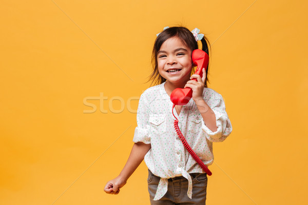 Stock photo: Happy excited little girl child talking by red retro telephone.