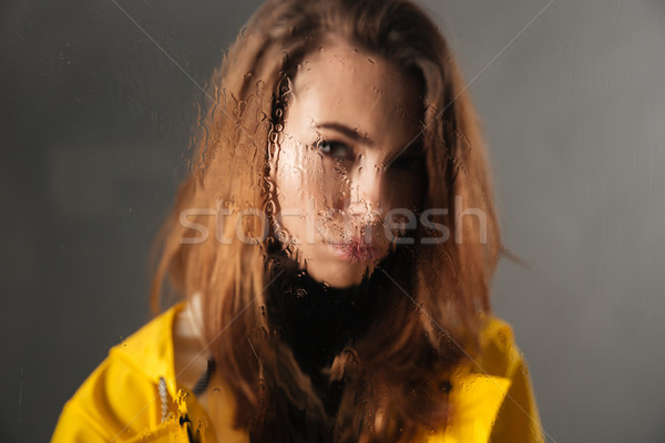Close up of a sad girl dressed in raincoat Stock photo © deandrobot