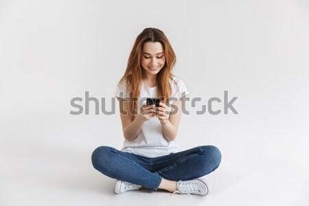 Photos jeune femme jeans séance jambes croisées Photo stock © deandrobot