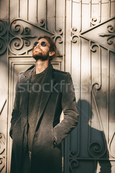 Portrait of a stylish bearded man in sunglasses and coat Stock photo © deandrobot