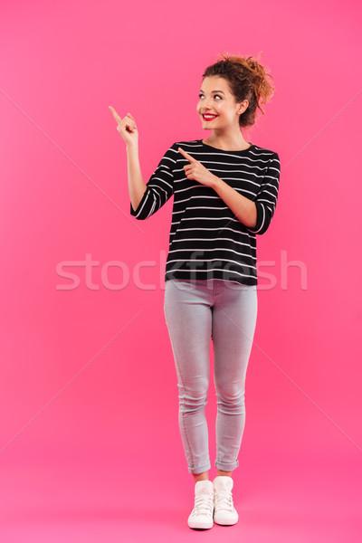 Tam uzunlukta portre genç gülen kız işaret Stok fotoğraf © deandrobot