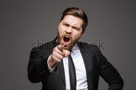 Portrait of a furious young businessman Stock photo © deandrobot
