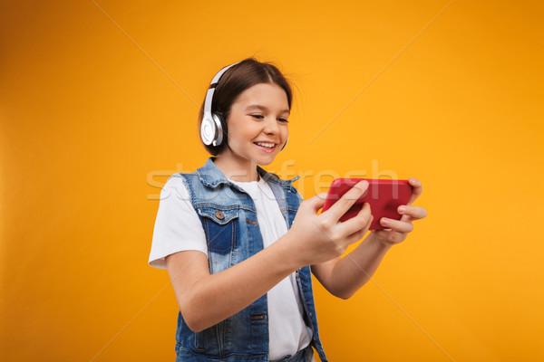 портрет удовлетворенный мало школьница наушники Сток-фото © deandrobot