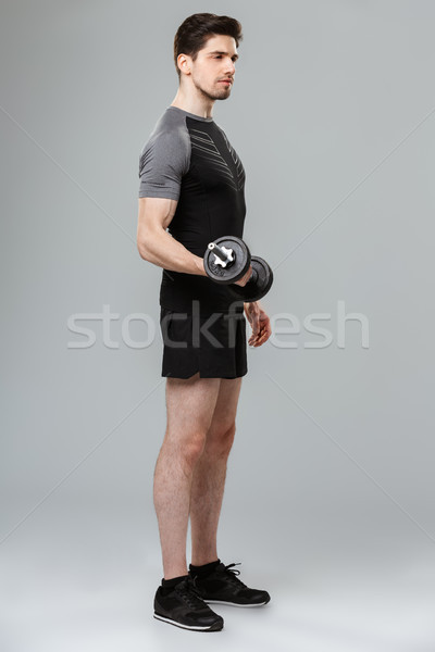 Concentrated young sportsman make sport exercises with dumbbell. Stock photo © deandrobot
