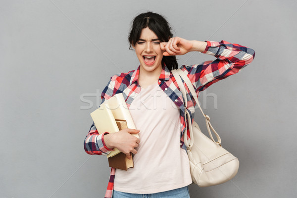 Sad displeased young lady holding books. Stock photo © deandrobot