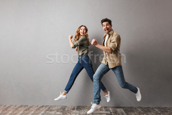 Full length portrait of a happy young couple jumping Stock photo © deandrobot