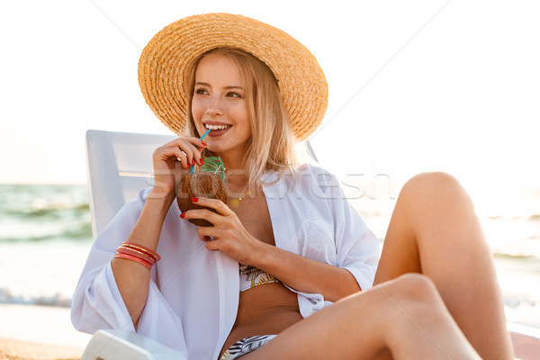 Photo of attractive blonde woman 20s in straw hat drinking exoti Stock photo © deandrobot