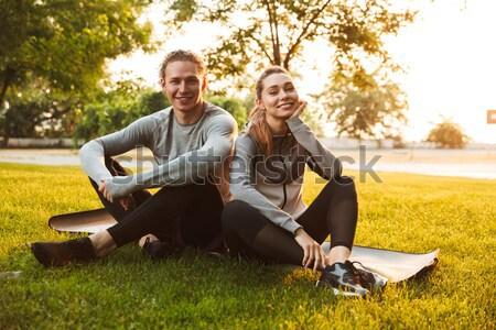Sport loving couple friends sitting in park Stock photo © deandrobot