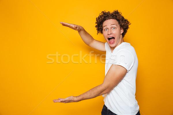 Jovem animado homem 20s marrom cabelos cacheados Foto stock © deandrobot