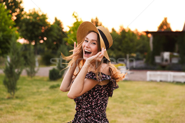 Photo of happy caucasian woman 20s wearing straw hat and dress s Stock photo © deandrobot