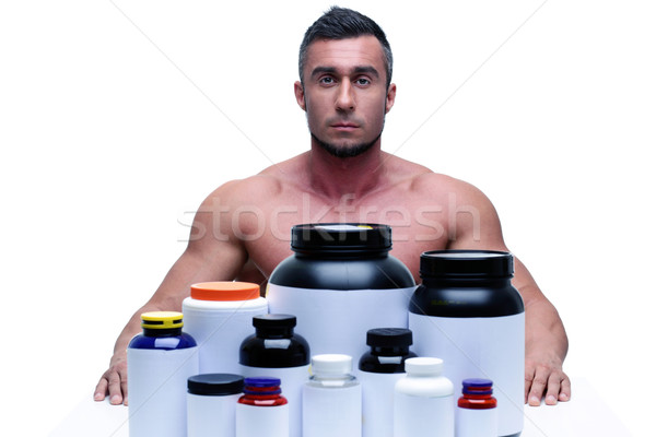 Muscular man sitting at the table with sports nutrition Stock photo © deandrobot