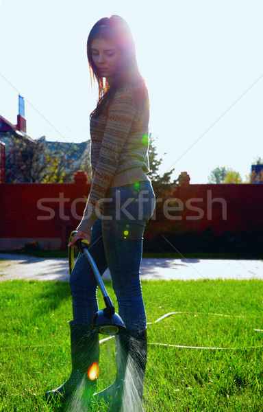 Full-length portrait of a woman is watering a garden Stock photo © deandrobot