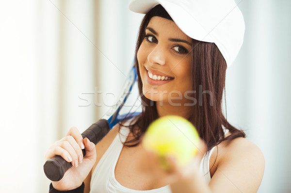 Stock photo: Healthy happy woman poses with a tennis racket while holding tennis ball