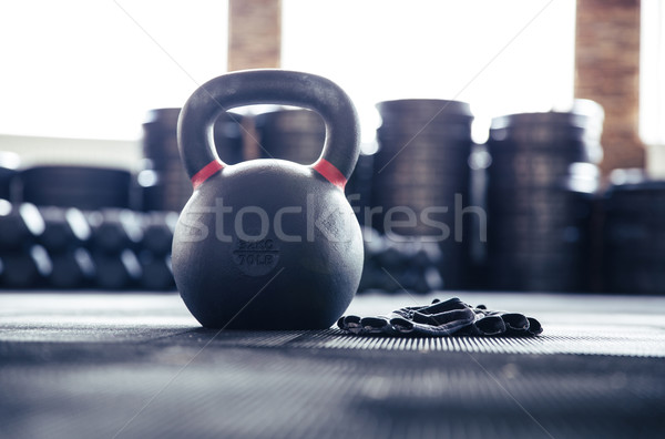 Closeup image of a kettle ball and sports gloves Stock photo © deandrobot