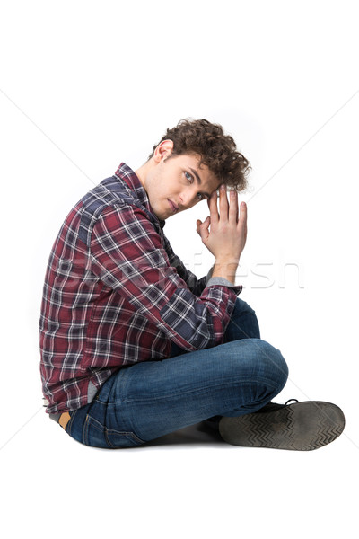 Side view portrait of a young man sitting on the floor Stock photo © deandrobot