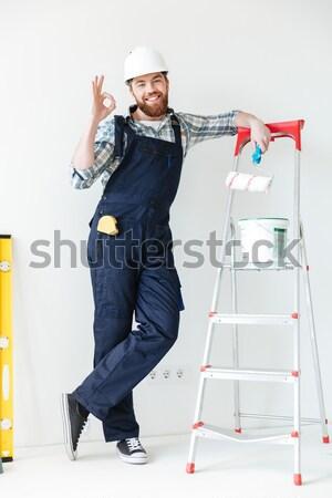 Fiatal jóképű férfi dob pénz levegő szürke Stock fotó © deandrobot