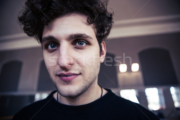 Portrait of a handsome man with curly hair looking at camera Stock photo © deandrobot