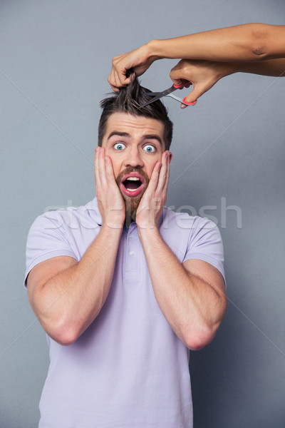 Man looking frightened while female hands cutting his hair Stock photo © deandrobot