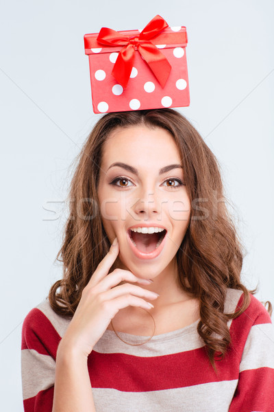 Amazed woman with gift box on head looking at camera Stock photo © deandrobot