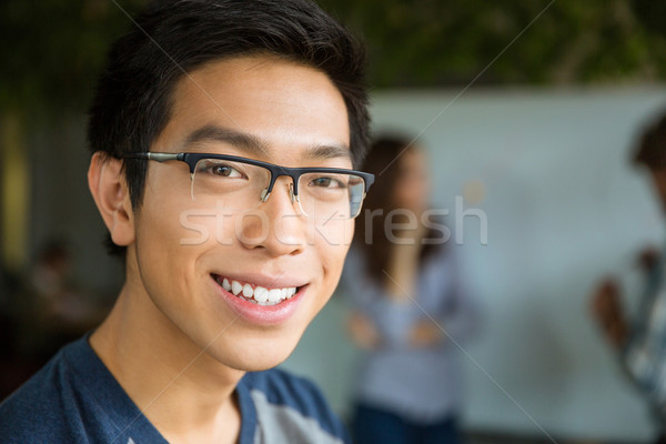 Closeup portrait of young positive asian man Stock photo © deandrobot