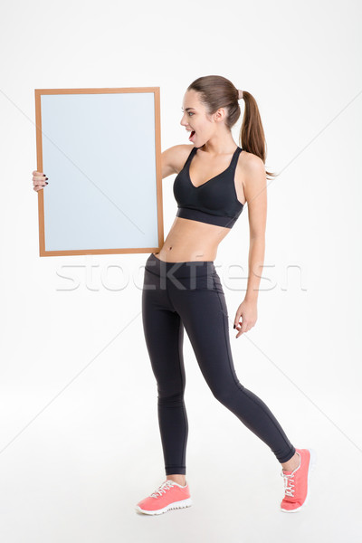 Gyönyörű boldog fiatal fitnessz nő tréningruha mutat Stock fotó © deandrobot