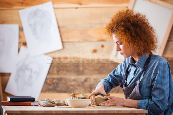 Serious woman potter creating dishes with clay by hands Stock photo © deandrobot