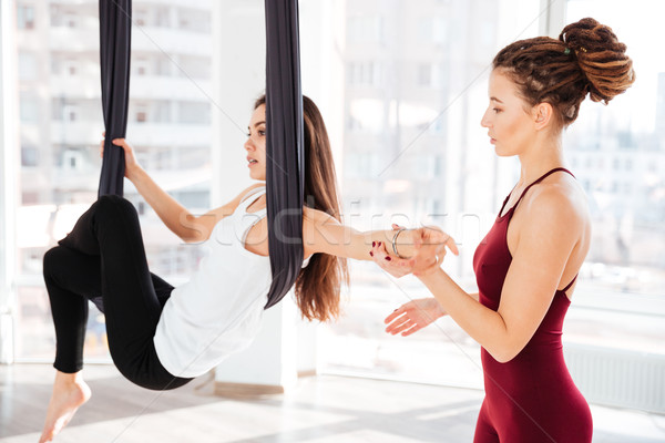Serious young woman trainer teaching beautiful girl doing aerial yoga Stock photo © deandrobot