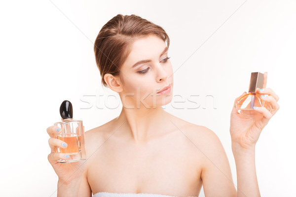 Attractive young woman holding two bottles of parfums  Stock photo © deandrobot