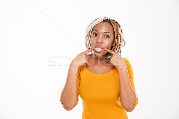 Playful amusing african american young woman showing tongue  Stock photo © deandrobot