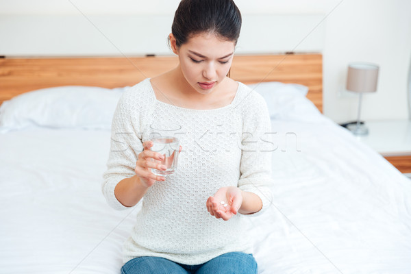 Sick woman holding pills and glass with water Stock photo © deandrobot